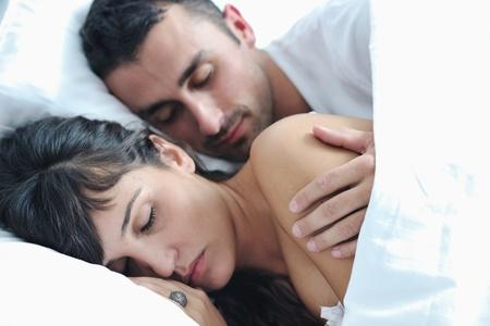 hacer el amor: feliz pareja de jóvenes saludables tienen buen tiempo en su dormitorio hacer el amor y dormir