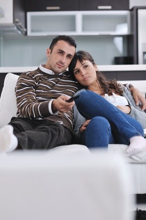 Relaxed young  couple watching tv at home in bright living room photo