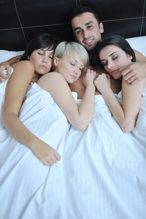 successful Young handsome man lying in bed with three sleeping girls Stock Photo - 13235708