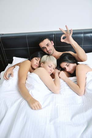 successful Young handsome man lying in bed with three sleeping girls Stock Photo - 13276384