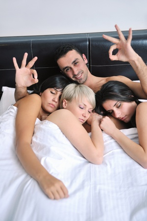 successful Young handsome man lying in bed with three sleeping girls Stock Photo - 13276529