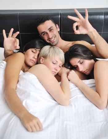 Erfolgreiche junge sch�ne Mann im Bett liegend mit drei schlafenden M�dchen Stockfoto - 13276524