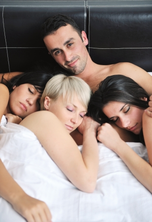 sexo cama: exitoso hombre guapo joven tumbado en la cama con tres chicas para dormir