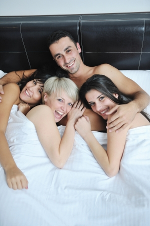 adult sex: successful Young handsome man lying in bed with three sleeping girls