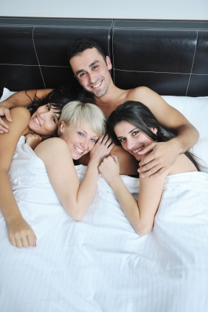 naked young people: successful Young handsome man lying in bed with three sleeping girls