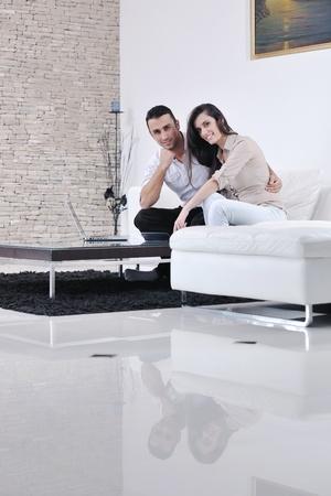 pareja en casa: pareja feliz relajarse y trabajar en la computadora port�til en casa moderna sala de estar interior