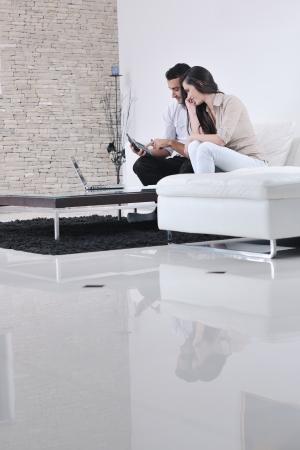 pareja feliz relajarse y trabajar en la computadora portátil en casa moderna sala de estar interior