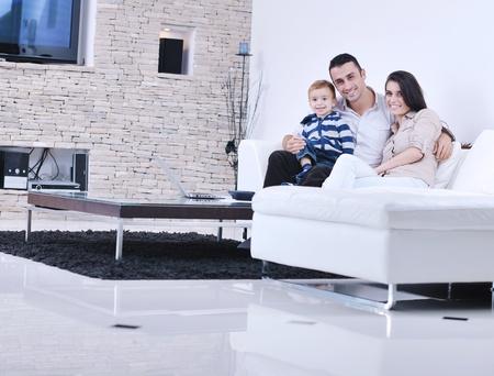 convivencia familiar: joven familia feliz divertirse y descanso en su casa nueva con un moderno televisor LCD en el fondo