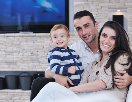 family on couch: happy young family have fun and relaxing at new home with modern lcd tv in background