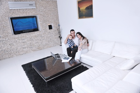 happy young family have fun and relaxing at new home with modern lcd tv in background photo