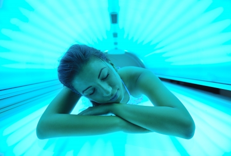 Beautiful young woman have tanning skin treatment in modern solarium photo