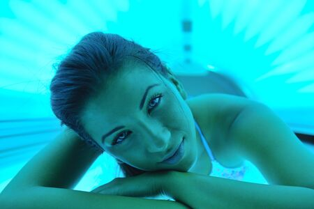 lady with the lamp: Beautiful young woman have tanning skin treatment in modern solarium