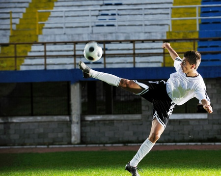 world cup: soccer player doing kick with ball on football stadium  field  isolated on black background  in night