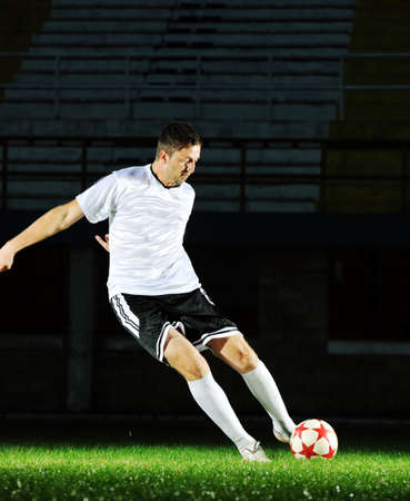 world player: soccer player doing kick with ball on football stadium  field  isolated on black background  in night