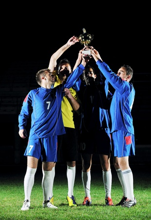 sport celebration: football players team group celebrating the victory and become champion of game while holding win coup Stock Photo