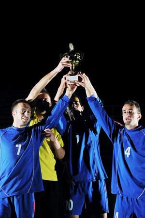 team winner: football players team group celebrating the victory and become champion of game while holding win coup Stock Photo