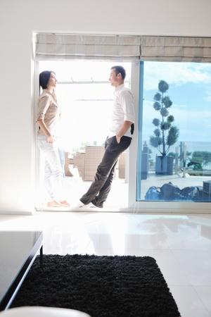 現代家のリビング ルームの室内でリラックスして幸せな若いカップル