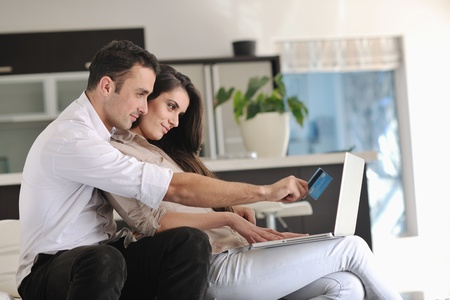 finance girl: joyful couple relax and work on laptop computer at modern living room indoor home Stock Photo