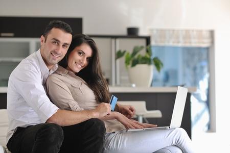 parejas felices: pareja feliz relajarse y trabajar en la computadora port�til en casa moderna sala interior Foto de archivo