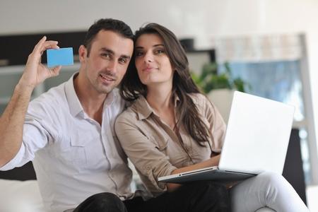 coppia in casa: coppia gioioso relax e lavorare con il computer portatile a casa moderna sala interna