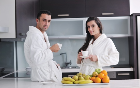 happy young couple have fun in  modern kitchen indoor  while preparing fresh fruits and vegetables food salad photo