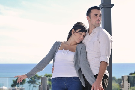 happy young couple relax on balcony outdoor with ocean and blue sky in background Stock Photo - 11398843