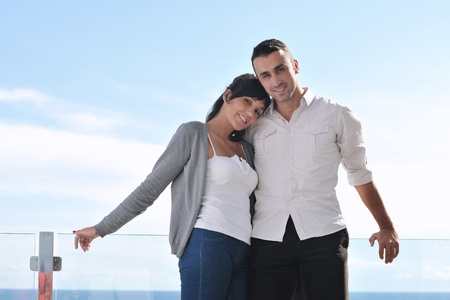 happy young couple relax on balcony outdoor with ocean and blue sky in background Stock Photo - 11398848