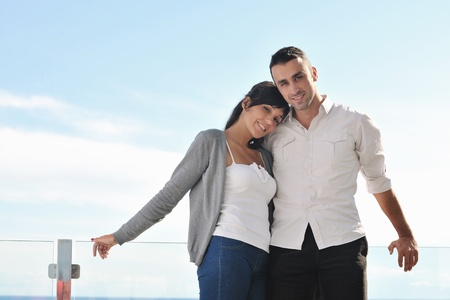 happy young couple relax on balcony outdoor with ocean and blue sky in background Stock Photo - 11398838