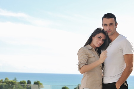 romantic sky: happy young couple relax on balcony outdoor with ocean and blue sky in background