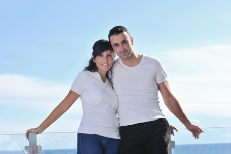 happy young couple relax on balcony outdoor with ocean and blue sky in background Stock Photo - 11398845