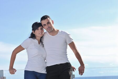 happy young couple relax on balcony outdoor with ocean and blue sky in background Stock Photo - 11398840