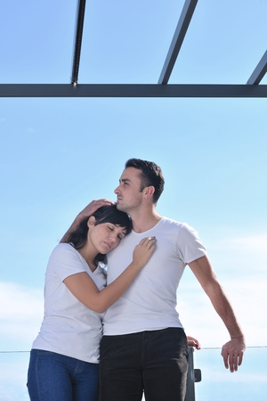 happy young couple relax on balcony outdoor with ocean and blue sky in background photo