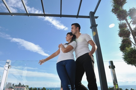 happy young couple relax on balcony outdoor with ocean and blue sky in background Stock Photo - 11398883