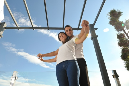 happy young couple relax on balcony outdoor with ocean and blue sky in background Stock Photo - 11398878