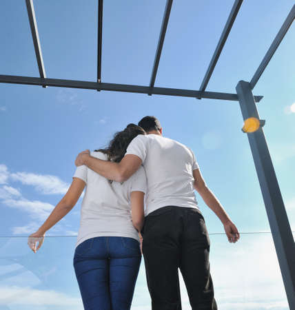 happy young couple relax on balcony outdoor with ocean and blue sky in background Stock Photo - 11398826