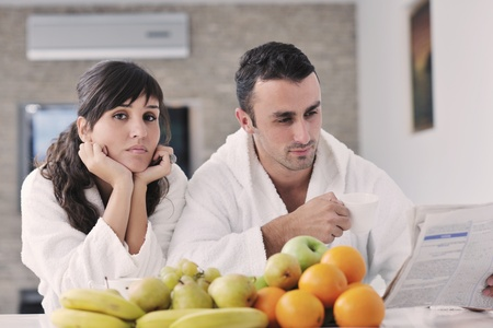 young family couple read newspaper at kitchen in morning with  fresh breakfast  fruits food and coffee drink on table Stock Photo - 11398841