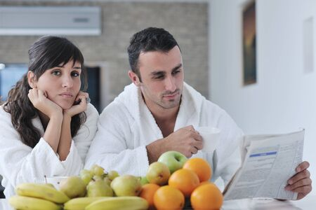 young family couple read newspaper at kitchen in morning with  fresh breakfast  fruits food and coffee drink on table Stock Photo - 11422734