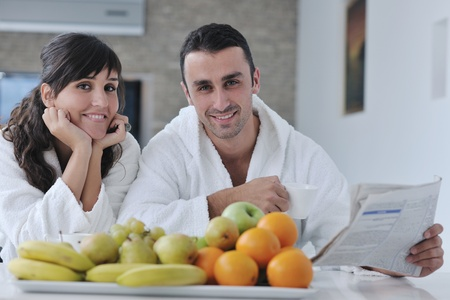 young family couple read newspaper at kitchen in morning with  fresh breakfast  fruits food and coffee drink on table Stock Photo - 11398911