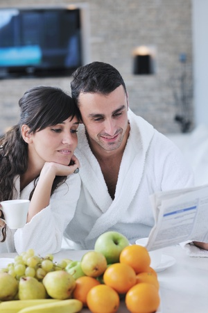 young family couple read newspaper at kitchen in morning with  fresh breakfast  fruits food and coffee drink on table Stock Photo - 11398915
