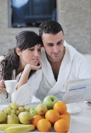 young family couple read newspaper at kitchen in morning with  fresh breakfast  fruits food and coffee drink on table Stock Photo - 11398914