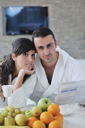 young family couple read newspaper at kitchen in morning with  fresh breakfast  fruits food and coffee drink on table Stock Photo - 11422742