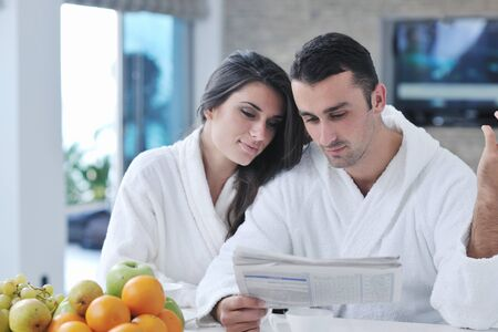 young family couple read newspaper at kitchen in morning with  fresh breakfast  fruits food and coffee drink on table Stock Photo - 11422727
