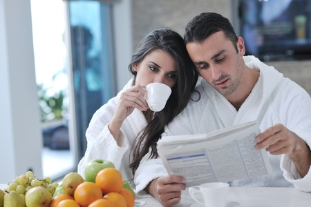 newspaper reading: young family couple read newspaper at kitchen in morning with  fresh breakfast  fruits food and coffee drink on table