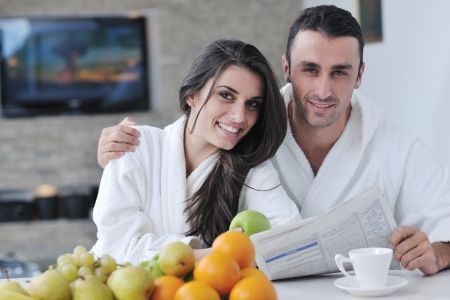 young family couple read newspaper at kitchen in morning with  fresh breakfast  fruits food and coffee drink on table photo