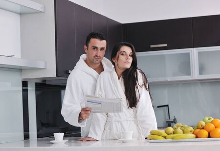 young family couple read newspaper at kitchen in morning with  fresh breakfast  fruits food and coffee drink on table Stock Photo - 11422715