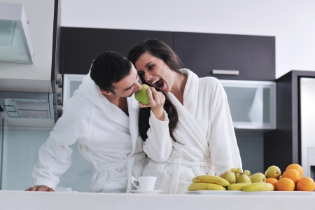 family kitchen: happy young couple have fun in  modern kitchen indoor  while preparing fresh fruits and vegetables food salad Stock Photo