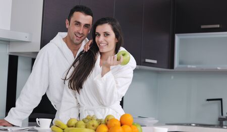 happy young couple have fun in  modern kitchen indoor  while preparing fresh fruits and vegetables food salad Stock Photo - 11422729