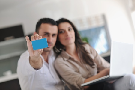 secure money: joyful couple relax and work on laptop computer at modern living room indoor home Stock Photo
