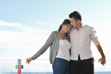 happy young couple in love have romance  relax on balcony outdoor with ocean and blue sky in background photo