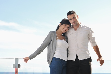 balcony view: happy young couple in love have romance  relax on balcony outdoor with ocean and blue sky in background